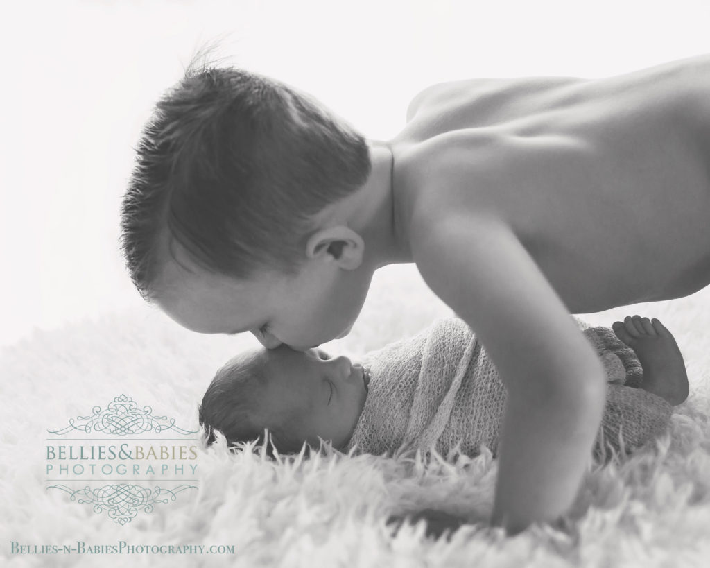 Big brother kissing little brother, black white