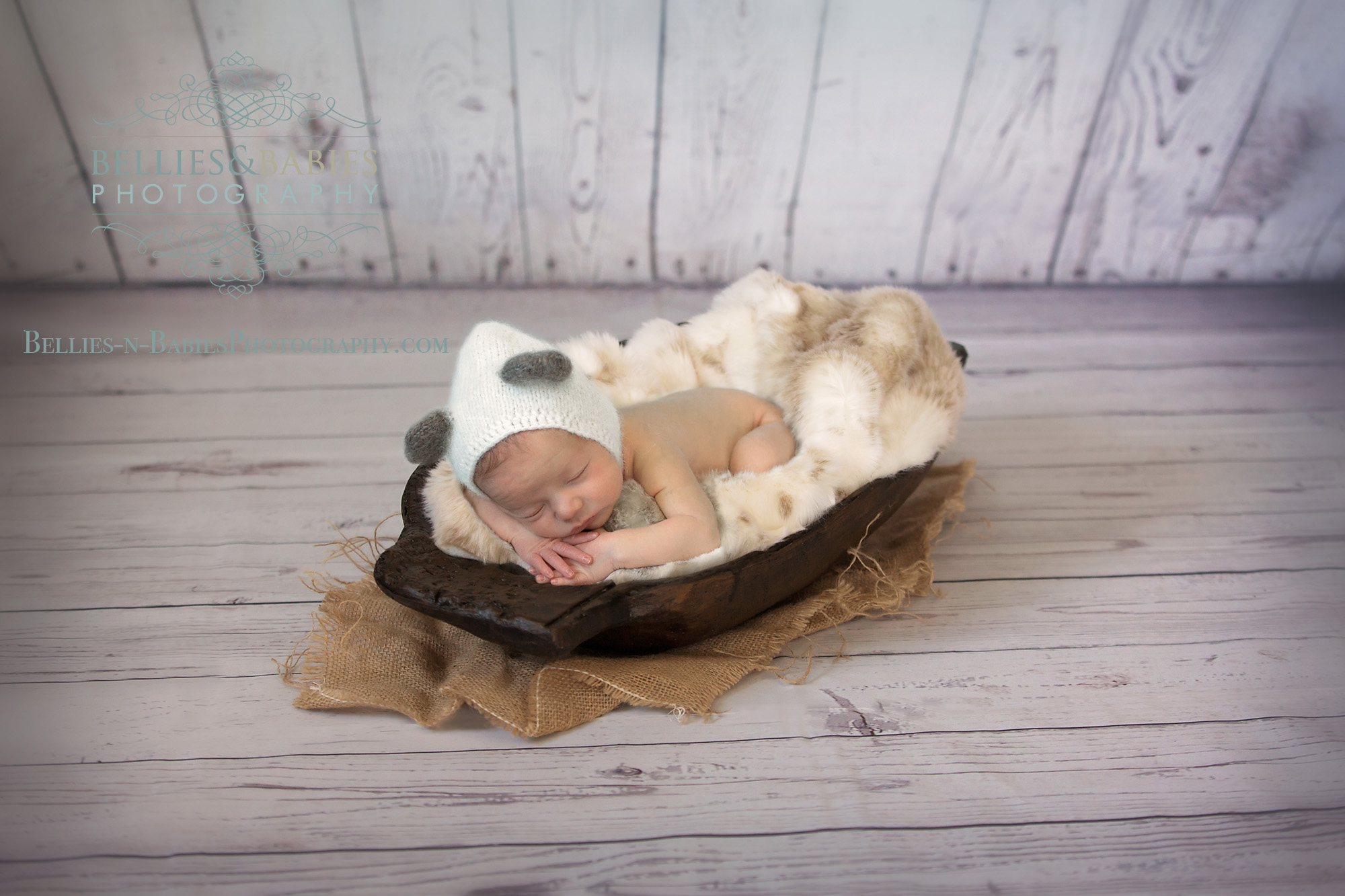 newborn in trencher bowl, fur, wood wall